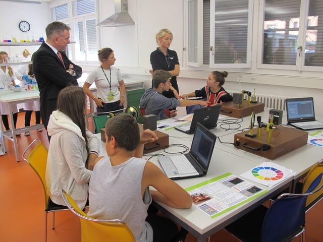Jugendliche sitzen an einem Tisch mit Laptops und Unterlagen. Landammann Alex Hürzeler und iLAB-Lehrerin Andrea Walther stehen daneben.