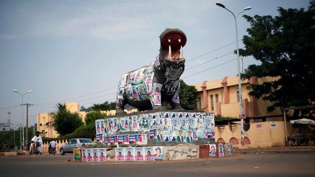 Eine Verkehrsinsel, auf der ein grosses Nilpferd aus Stein steht, ist vollgekleistert mit Wahlplakaten.