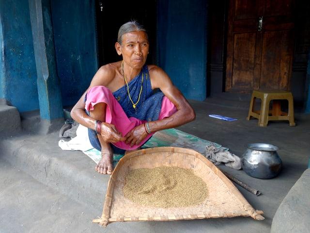 Eine indishce Frau kniet vor einer Schaufel voll Hirse.