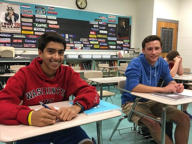 Zwei Schüler an ihren Pulten, sie lächeln in die Kamera.