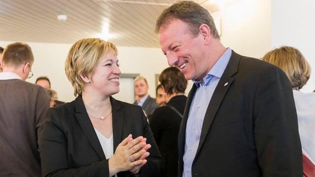Die beiden Kandidierenden lachen gemeinsam.