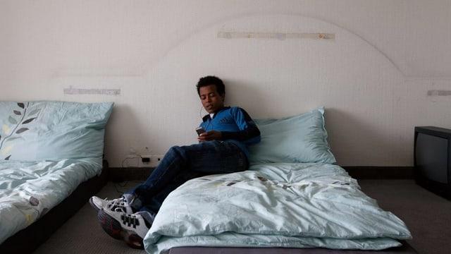 Ein Asylsuchender sitzt auf einem Bett