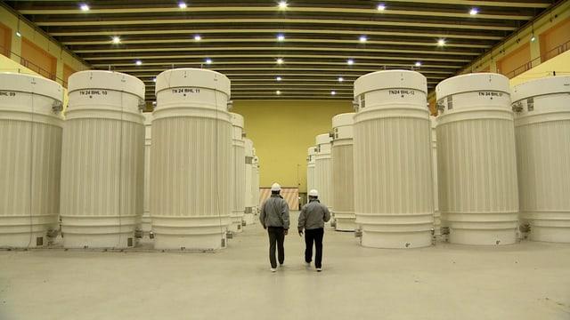 Grosse Behälter, dazwischen laufen zwei Männer.
