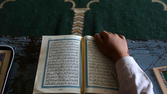 Ein Schüler sitzt vor einem Koran.
