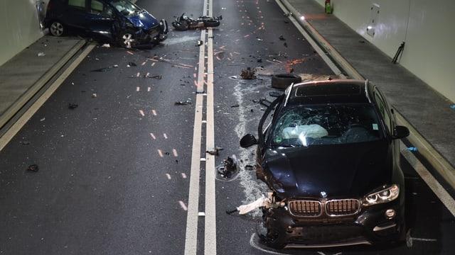 Ein stark beschädigtes Auto in einem Tunnel, im Hintergrund ein weiteres Auto und ein Töff.