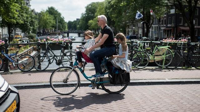 Ein Vater mit zwei Kindern auf dem Velo.
