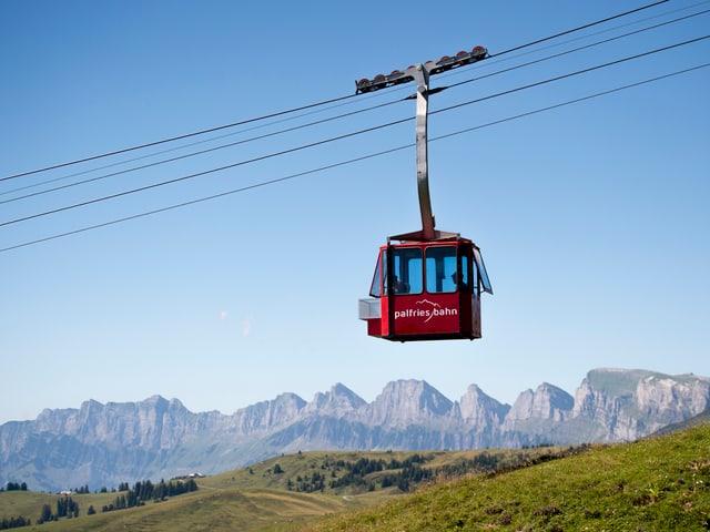 Rote Gondel mit Schriftzug Palfries vor Bergpanorama.