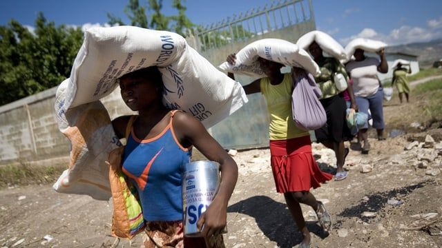 Persunas dal Haiti che portan satgs da nutriment.