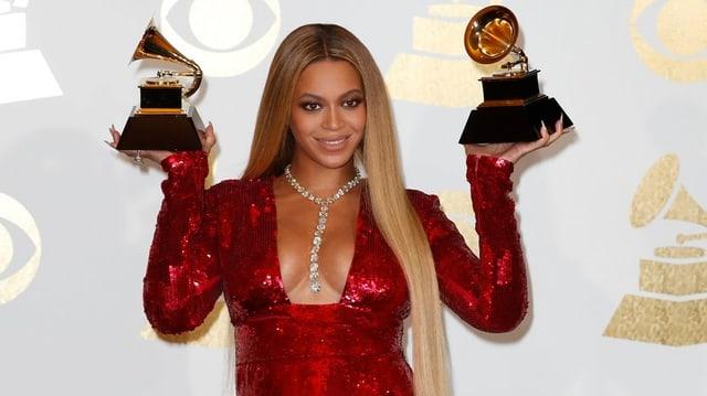 Beyoncé hält Grammy-Auszeichnungen in den Händen.