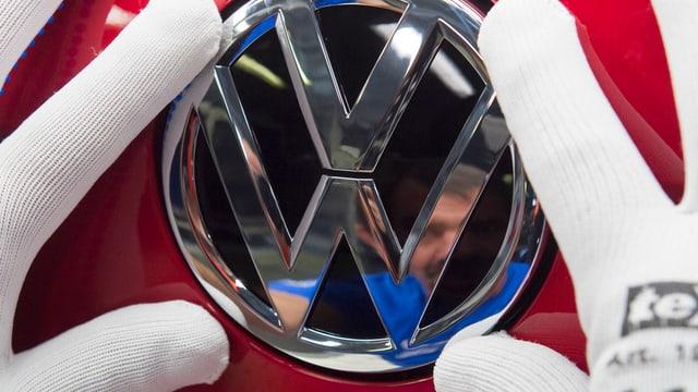 Hände in weissen Handschuhen halten das Zeichen für VW.