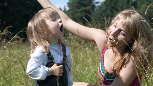 Eine Frau und ein Kind singen auf einer Wiese in der Sonne.