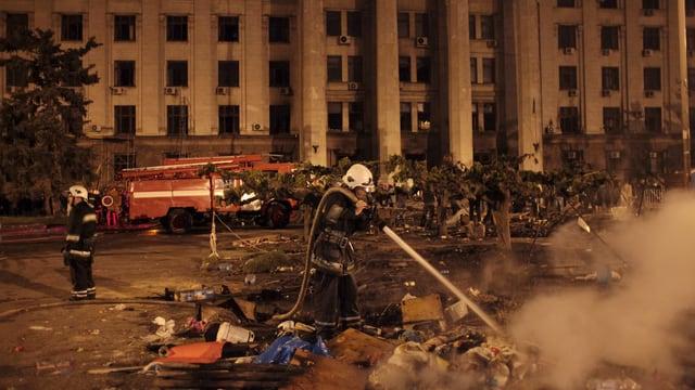 Ein Feuerwehrmann löscht Feuer vor einem Gebäude
