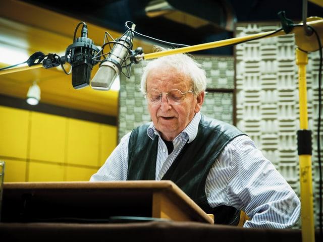 Peter Bichsel in hellem Hemd und Ledergilet sitzt an einem Tisch in einem Tonstudio und liest aus einem Text.