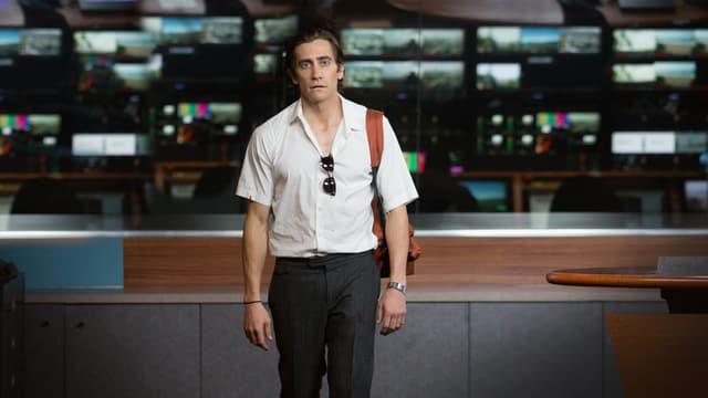 Reporter Lou Bloom frontal zur Kamera mit Sonnenbrille im weissen Hemd und herunterhängenden Schultern und einer braunen Tasche umgehängt