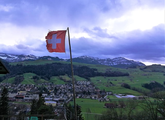 Zerrissene Schweizer Fahne. Im Hintergrund die Pilatuskette.
