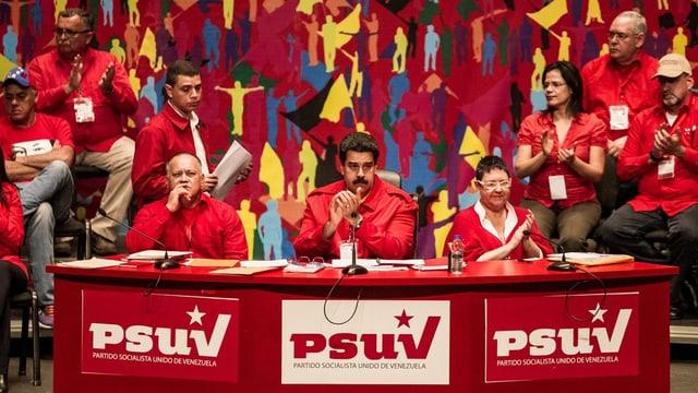 Präsident Maduro sitzt auf einem Podest umgeben von anderen Sozialisten.