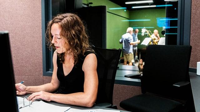 Ein Frau sitzt in einem Raum vor einem Zettel. Hinter ihr sieht man durch ein Fenster in ein Radiostudio.