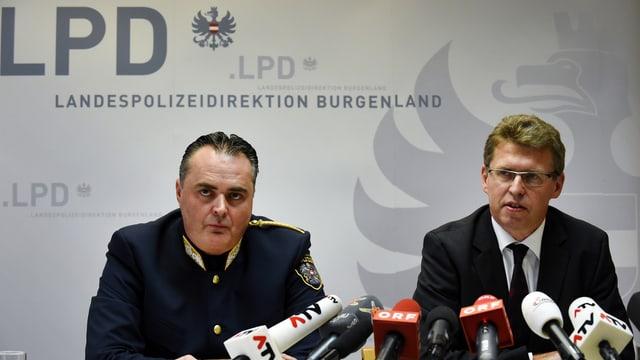 Zwei Männer an Pressekonferenz, vor ihnen mehrere Mikrofone.