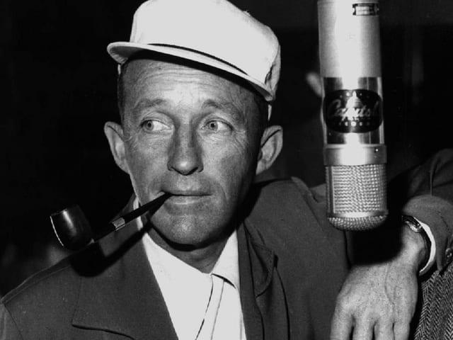 Ein Mann mit weissem Hut und Tabakpfeife vor einem Mikrofon.