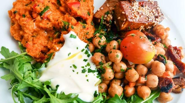 Ein Teller mit vegetarischen Zutaten wie zum Beispiel Tofu, Kichererbsen und Rucola.