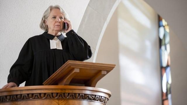 Eine Pfarrerin steht auf der Kanzel in einer Kirche. Sie hält sich ein Handy ans Ohr und schaut ernst geradeaus.