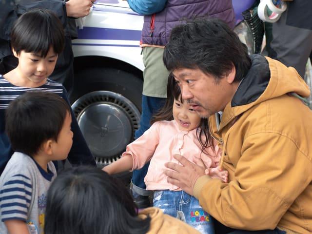 Der Regisseur spricht mit drei Kindern.