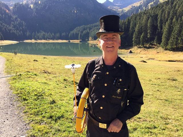 Kaminfeger mit schwarzer Uniform und Zylinder lächelt in die Kamera.