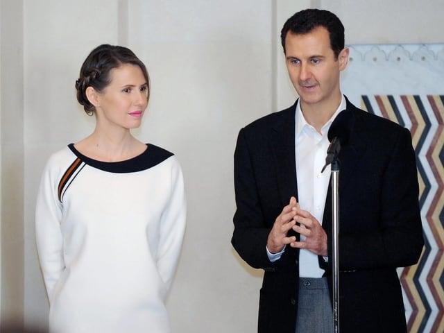 Assad redet in ein Mikrophon, seine Frau steht neben ihm