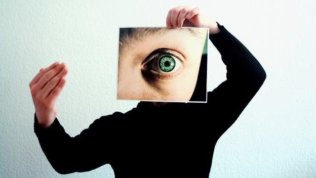 Ein Mensch hält ein Foto eines weit geöffneten Auges vor sein Gesicht.
