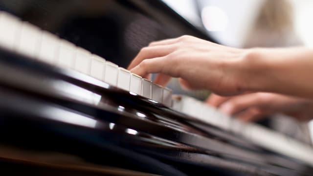 Zwei Hände beim Klavierspiel.