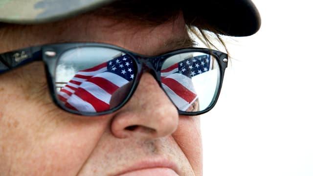 Ein Mann mit Sonnenbrille, in deren Gläser sich die amerikanische Flagge spiegelt.