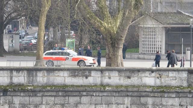 Ein Polizeiauto steht am Aareufer, zwei Polizisten kontrollieren einen Passanten.