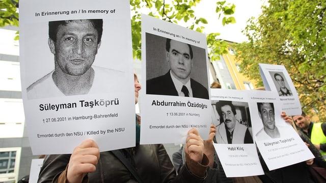 Demonstranten halten zum Prozessauftakt am 6. Mai 2013 in München Bilder von NSU-Opfern in die Luft.