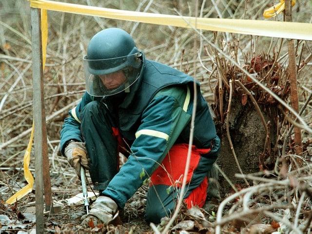 Ein Mann im grünen Schutzanzug entschärft eine Mine in Bosnien.