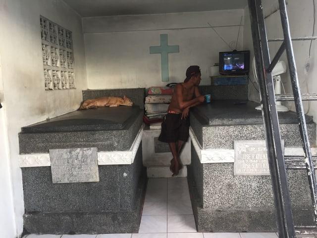 Ein Mann sitzt zwischen zwei Sarkophagen und schaut Fernsehen. Das Gerät steht auf dem einem Sarkophag, auf dem andern schläft ein Hund.