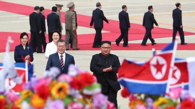 Moon und Kim mit ihren Frauen auf rotem Teppich, im Vordergrund Fahnen und Blumen.