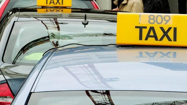 Taxi-Fahrzeuge stehen in einer Reihe.