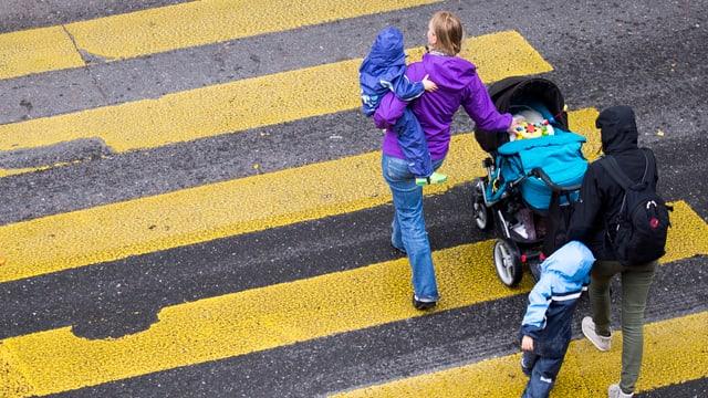Zwei Frauen gehen mit einem Kinderwagen und zwei Kindern über den Fussgängerstreifen.