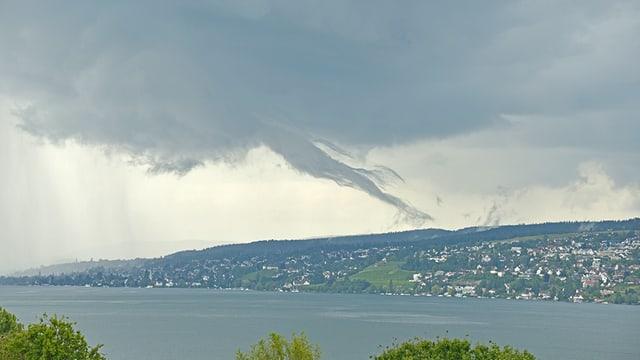Ein Wolkenrüssel ragt aus der Wolkenschicht heraus.