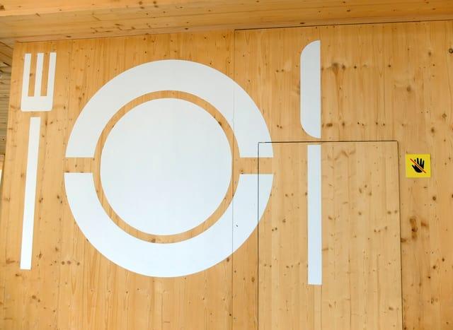 Riesiges Gabel-Teller-Messer-Piktogramm auf Holzwand.