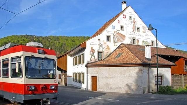 Waldenburgerbahn vor historischem Haus in Oberdorf.