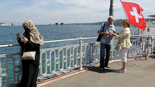 Eine verschleierte Frau steht am Ufer des Genfer Sees und schaut auf eine Karte. Ein Paar beobachtet sie dabei.