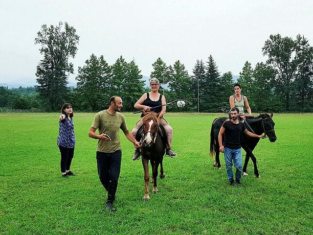 2 Frauen auf Pferden, die geführt werden.