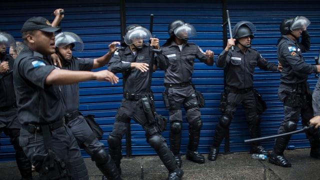 Symbolbild: Eine Reihe brasilianischer Polizisten in Kampfmontur mit erhobenen Schlagstöcken drängen sich an eine blaue Wand.