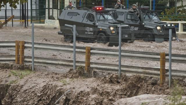 Militärfahrzeuge auf überfluteter Strasse.