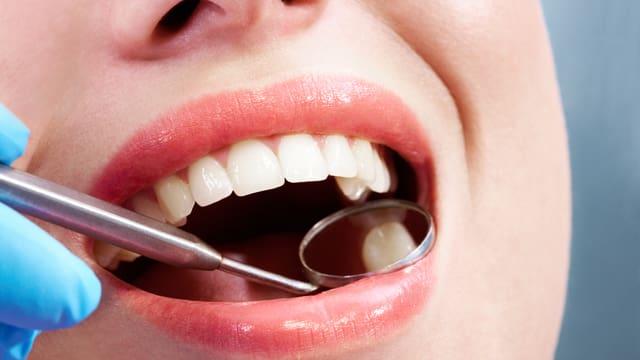Frau mit schönne Zähnen beim Zahnarzt