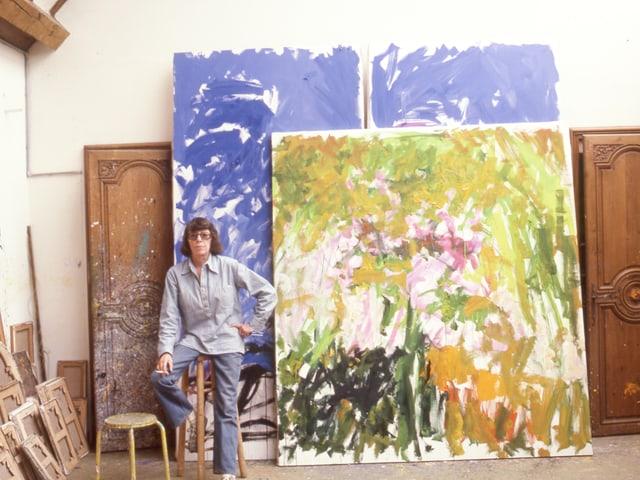 Eine Frau stitzt in einem Atelier vor zwei Gemälden.