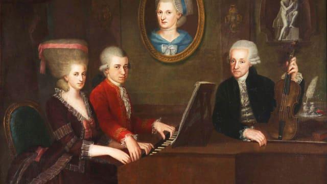 Gemälde: Wolfgang Amadeus Mozart mit seiner Schwester Maria Anna und Vater Leopold, an der Wand hängt ein Porträt der verstorbenen Mutter Anna Maria