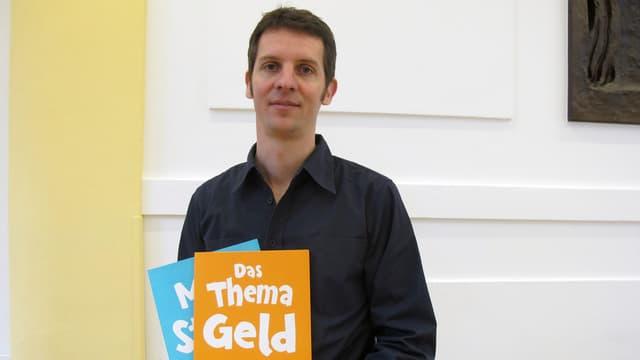 Mann mit zwei Broschüren in der Hand