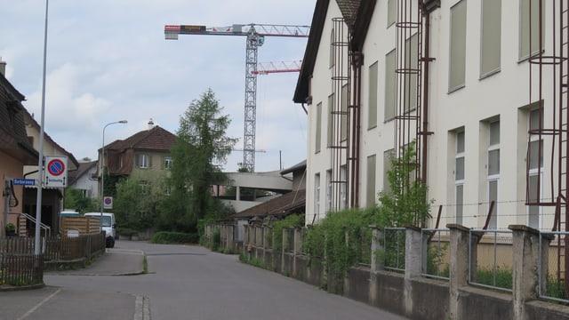 Strasse mit alten Häusern und Fabrik, im Hintergrund Baukran